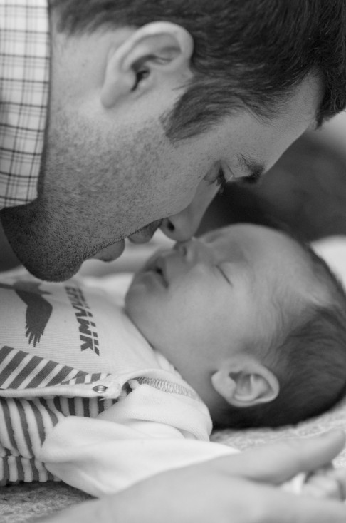 Black and white image of father touch his nose gently against his newborn's nose.
