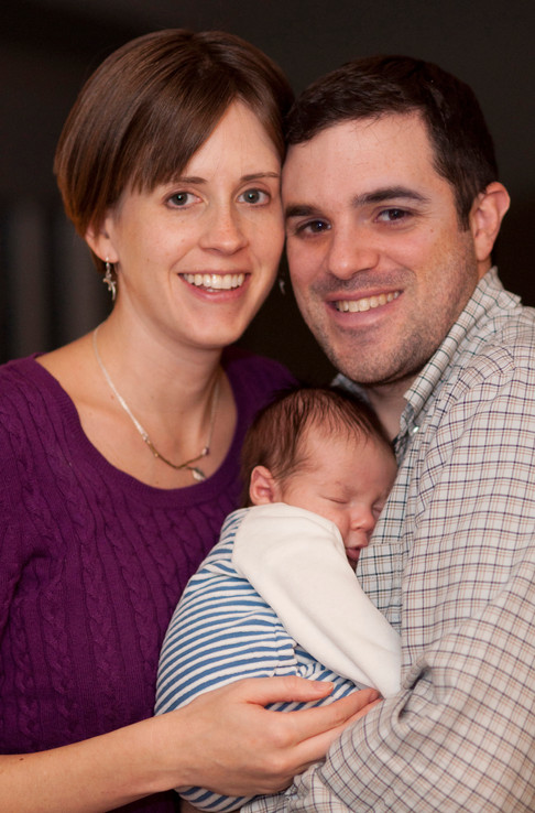White couple smile at the camera, holding their newborn between them.