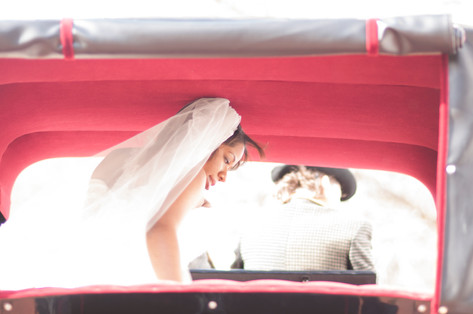 African american woman wearing wedding veil is backlit as she exits a red carriage.