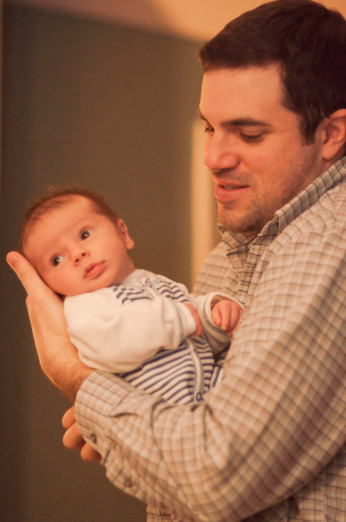 White father gently cradles his baby in his arm while supporting hishead in his palm.