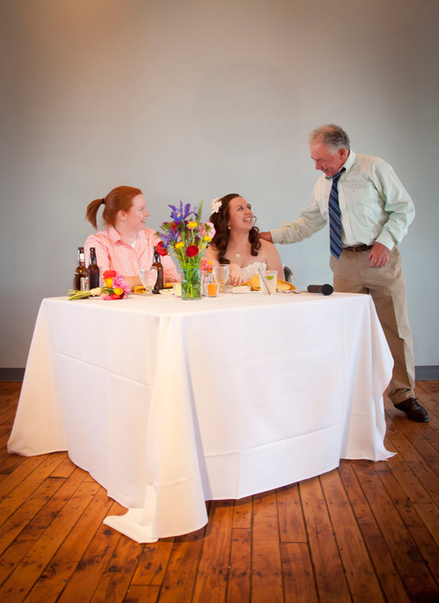 Bride and bride smile at wedding table as father of one of the brides leans in to offer advice.