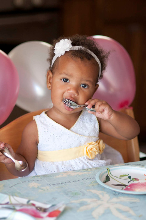 African american girl celebrates her 2nd birthday wearing a white and yellow dress.