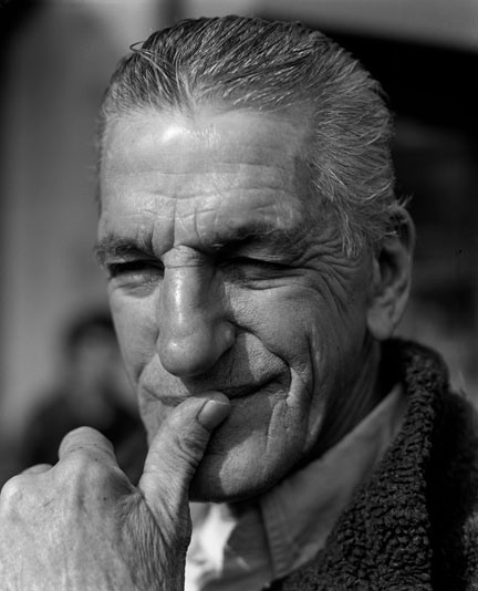 Black and white headshot of a white older man, with his thumb pressed to his lips, mimicking the gesture of the main character of the movie Breathless.