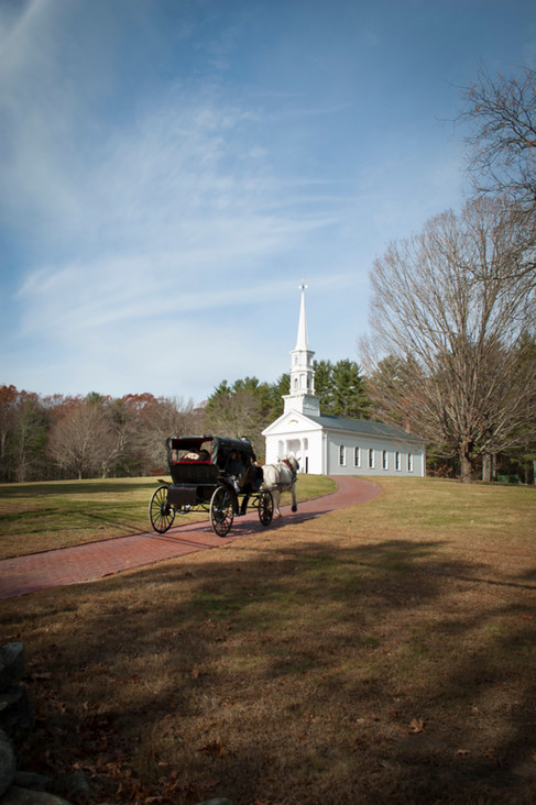 Wedding carriage approaches a small white church on a sunnny fall day.