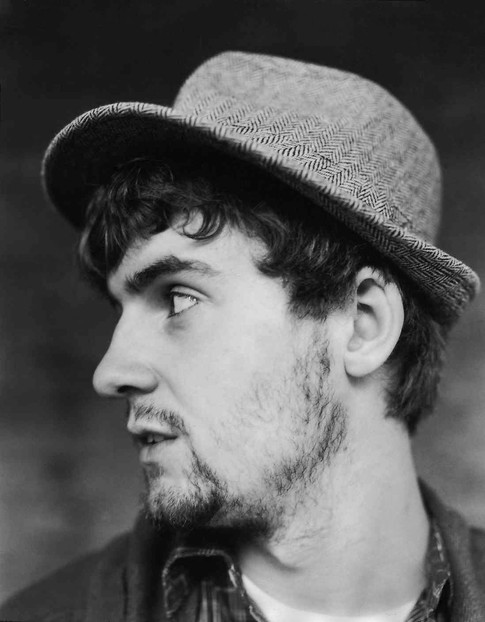 black and white profile image of a serious 20-something white man.