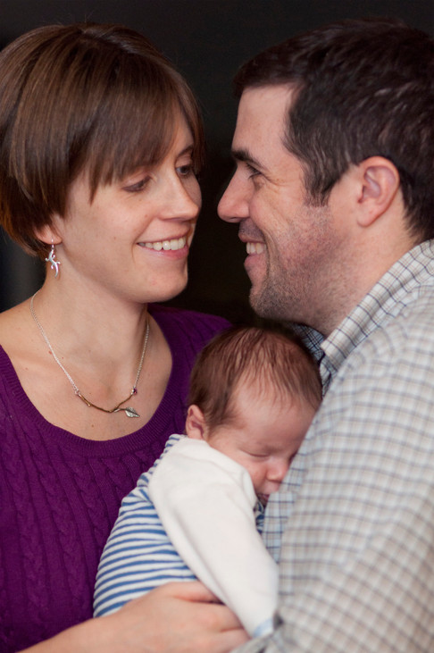 Husband and wife smile at each other while cradling newborn between them.