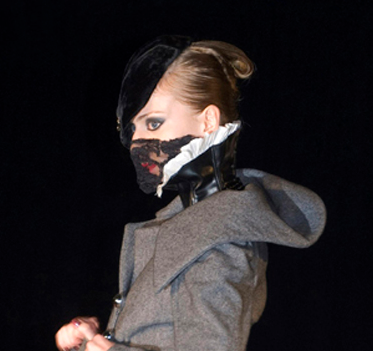 Close cropped image of a model in a fashion show, her face covered in lace.