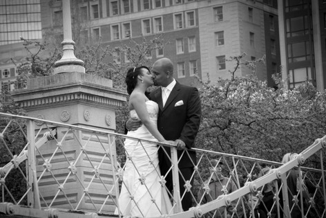 Black and white photo of african american bride and groom kissing on a bridge with the city buildings in the background.