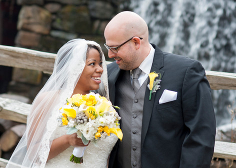 African american bride holds yellow bouquet while gazing lovingly at white groom in front of a small waterfall.