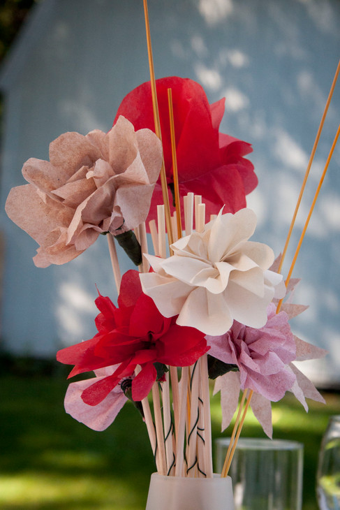 Pink, white, and red paper flowers in a bouquet.