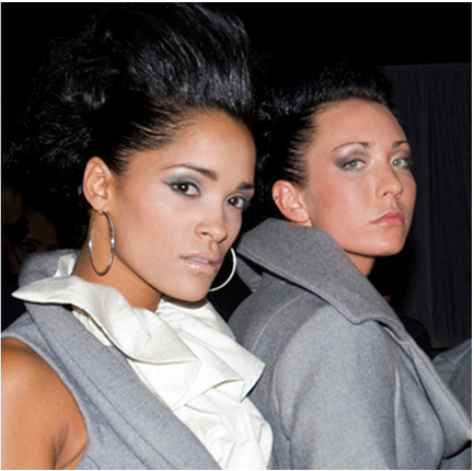 Two models pose in grey dresswear locking eyes with the camera.
