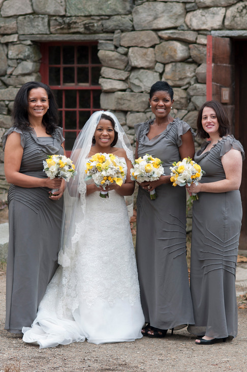 Bride stands at center, surrounded by bridesmaids, in front of stone building.