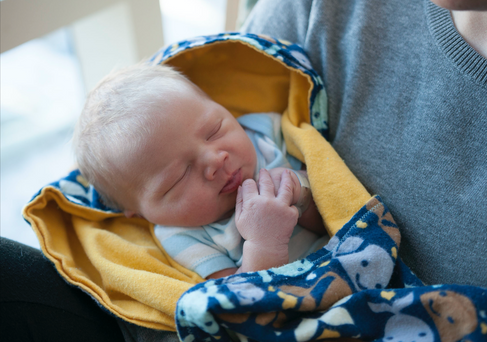 white newborn sleeps with hand pressed lightly to their lips.