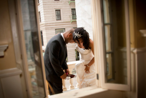 Groom and Bride stand on the balcony of the Old State House. Groom holds out the bride's shoe for her to step into.