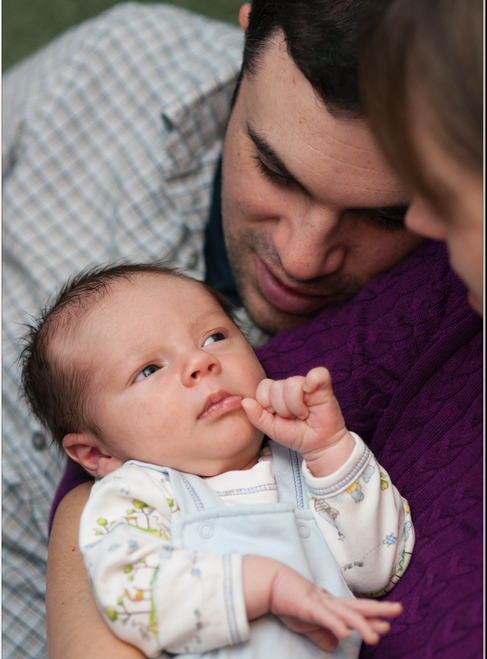 Man and woman gaze down at infant who stares at them.
