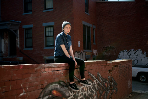 Young woman sits atop a brick graffiti covered fence. She offers a seriuos gaze to the camera.