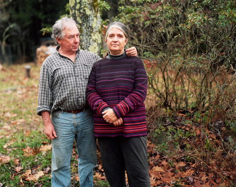 White couple in their 60s pose in casual clothing outdoors. Man puts his hand around his wife.