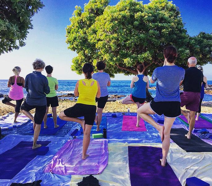 Yoga practice on beach in Hawaii tree pose ocean view