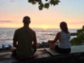 Sea wall meditation over ocean at sunset