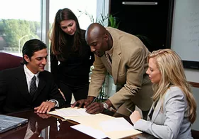 A group of persons look over a document.