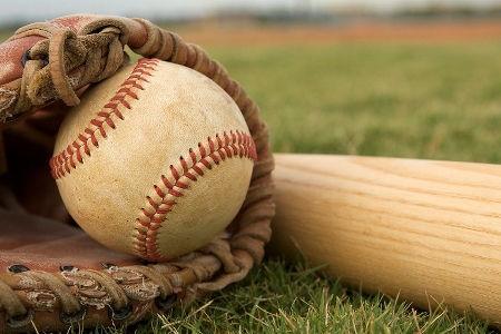 baseball glove holding baseball next to baseball bat on outfield grass of empty baseball field