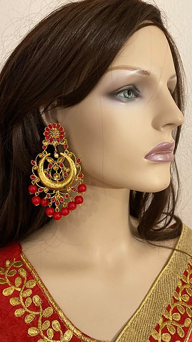 Big earrings with red pearls.