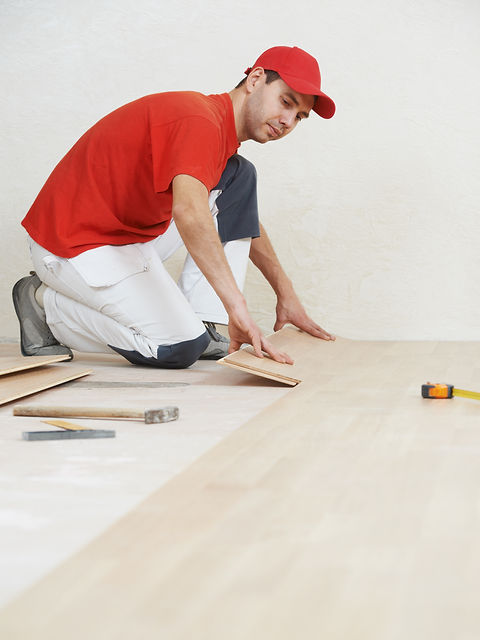 carpenter worker installing wood parquet