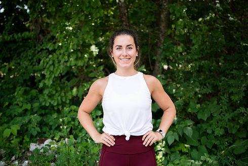 Woman standing confidently with her hands on her hips and smiling