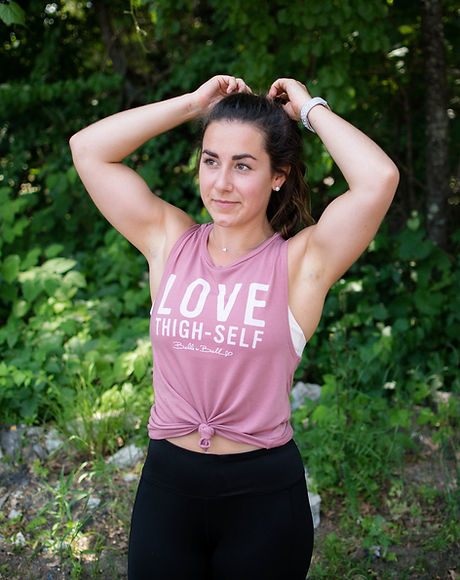 Woman wearing empowering tank top fixing pony tail looking away from camera