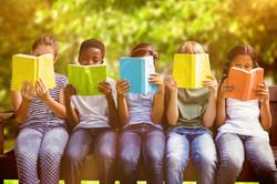 Children reading books at park against t