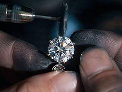 Ювелир полирует кольцо с крупным бриллиантом