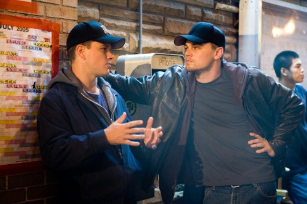 "MATT DAMON discusses a scene with LEONARDO DiCAPRIO on the set of Warner Bros. Pictures' crime drama ""The Departed."""