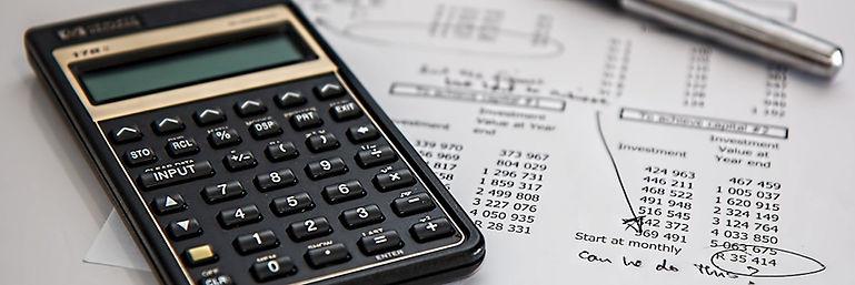 black-calculator-near-ballpoint-pen-on-w
