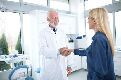 Dentist and patient shaking hand