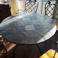 newer round metal and tile kitchen table with 4 metal and wood dining chairs with casters