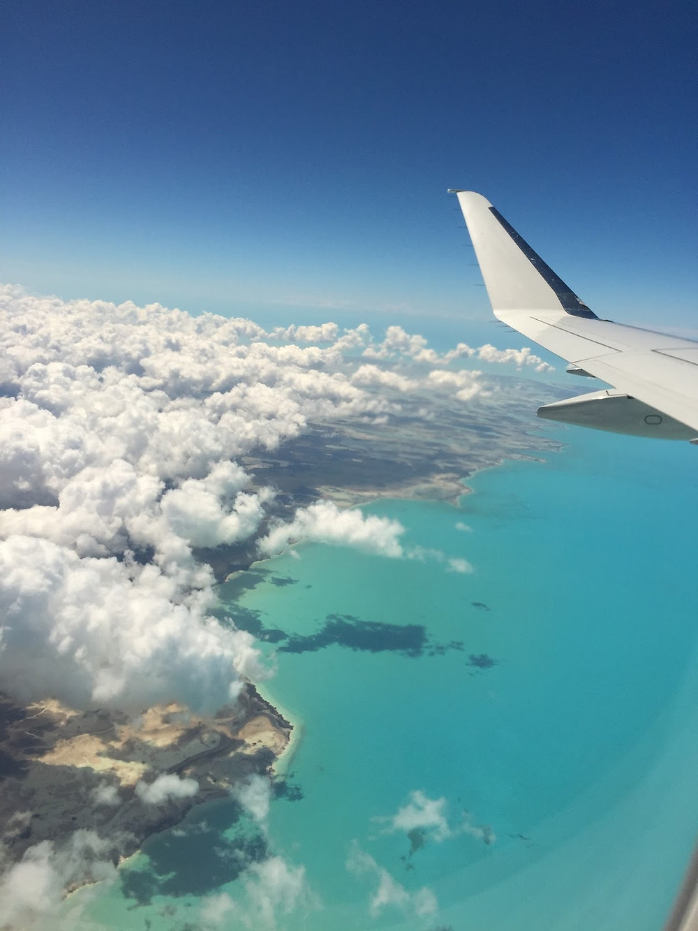 tail of an airplane flying over white cotton clouds and turquoise ocean