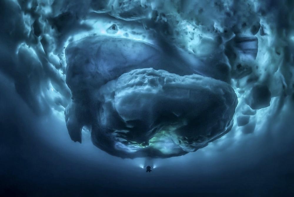 """""""Sub Zero"""" von Tobias Friedrich. Erster Platz: Die Schönheit der Natur. """"Taucher mit Lichtern in minus zwei Grad Celsius warmem Wasser in Ostgrönland unter dem Eis in einem zugefrorenen Fjord, der um Eisberge schwimmt""""."""
