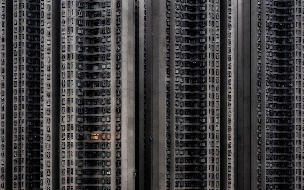 """""""Home Alone"""" von Attila Balogh. Erster Platz, Architektur und städtische Räume. """"Nur die Fenster einer einzigen Wohnung im Tsing Yi-Viertel, einem dicht besiedelten Gebiet Hongkongs, werden kurz vor Sonnenuntergang beleuchtet."""