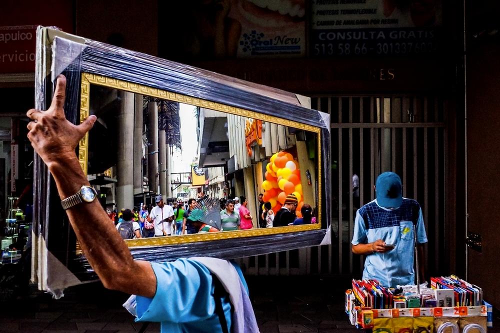 """""""Medellin-Mirror"""" von Michael Kowalczyk. Zweiter Platz, Straßenfotografie. """"Ein Mann mit einem blauen Hemd trägt einen großen neuen rechteckigen Spiegel auf seiner Schulter entlang der Straße und geht an einem Mann mit einem blauen Hemd vorbei, der hinter einem Verkaufsstand mit Handy-Zubehör in Medellin, Kolumbien, steht."""