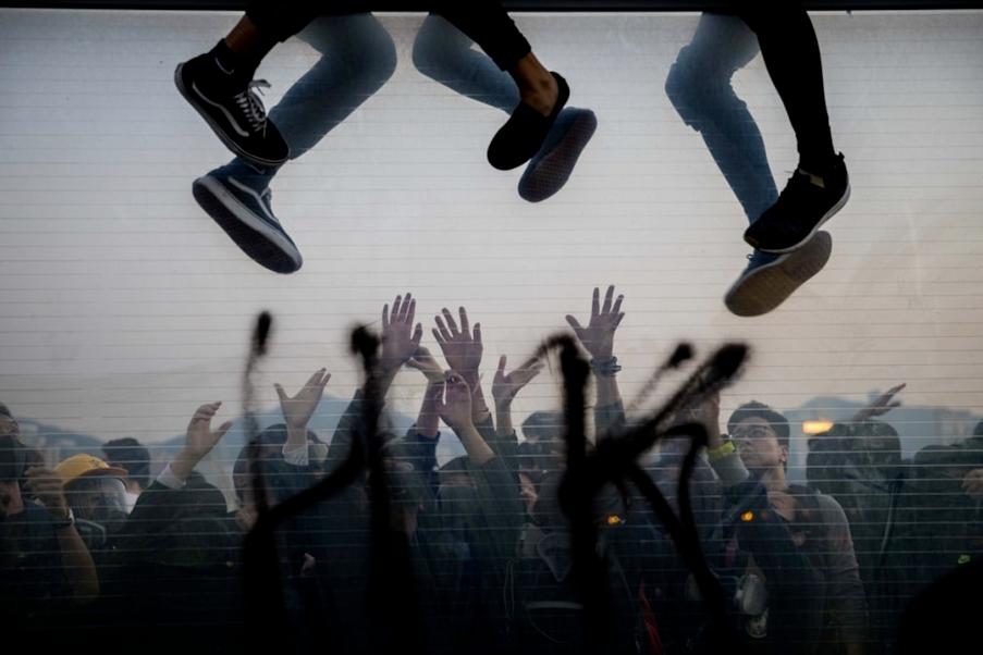 """""""Escaping"""" von Shawn Yuan. Dritter Platz, Dokumentar- und Fotojournalismus. """"Fliehende Demonstranten klettern über eine Autobahnbarrikade, um einem herannahenden Polizeifahrzeug auszuweichen, während andere während eines Marsches in Hongkong am 1. Dezember zur Unterstützung von der anderen Seite aus die Hand ausstrecken""""."""