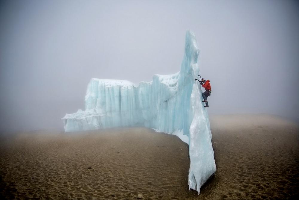 """""""Desert Ice"""" von Christian Pondella. Zweiter Platz, Sport in Aktion. """"Der professionelle Eiskletterer Will Gadd klettert auf das verbleibende Gletschereis am Krater des Kilimandscharo. Dieses Eis ist freistehend und sieht aus wie Eisberge auf dem Sand."""""""