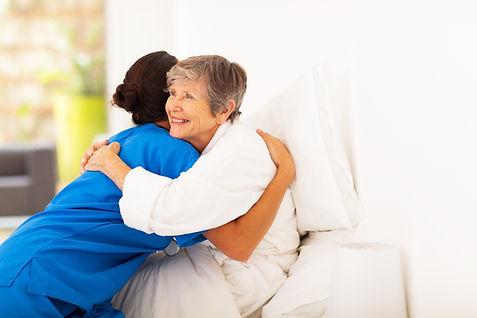 happy elderly woman hugging caregiver on