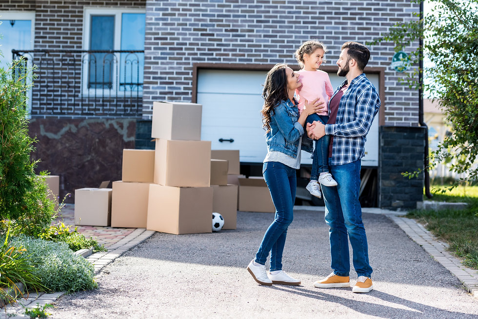 beautiful family in front of new house with many boxes standing on pathway to garage.jpg