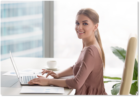 Attractive young woman at desk smiling with laptop