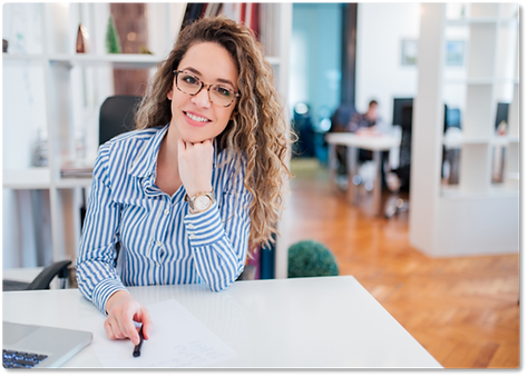 Pretty young woman in glasses sitting at desk