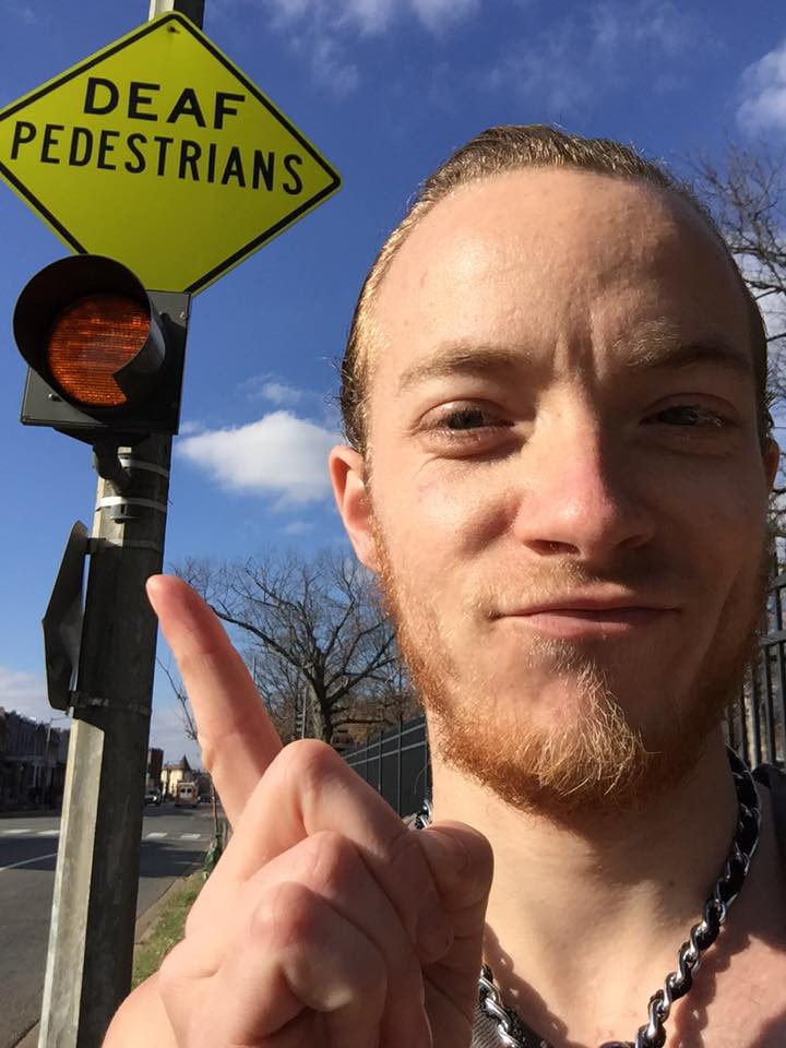 "photo of Cole Huff in front of a street sign that reads ""deaf pedestrians"""