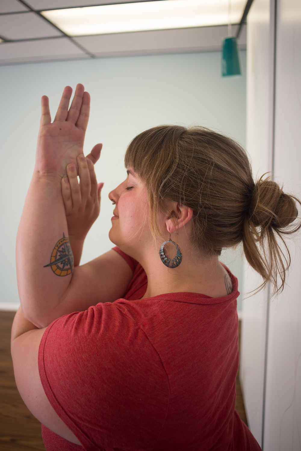 Melanie with arms wrapped like an eagle pose, eyes closed, in a yoga studio.