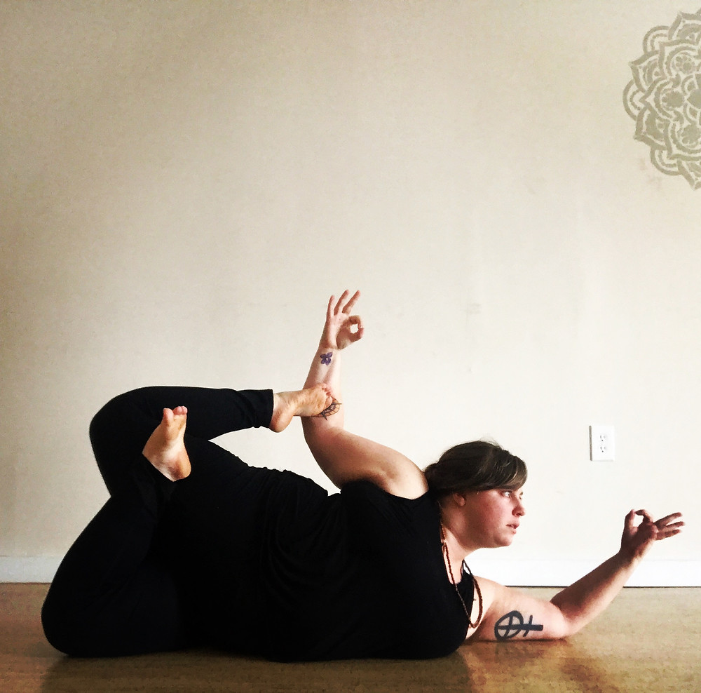 Melanie in a reclined yoga pose in a yoga studio.