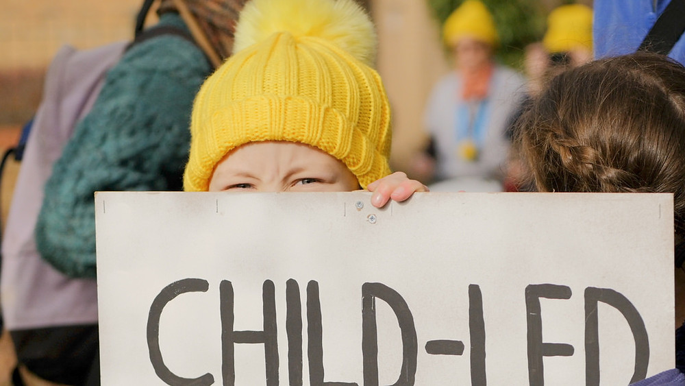 Child's face looking over placard with the words CHILD-LED written on it.