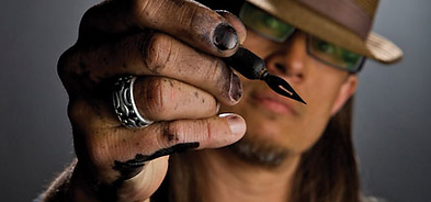 Graham Smith headshot 2, holding a pen with inked hands